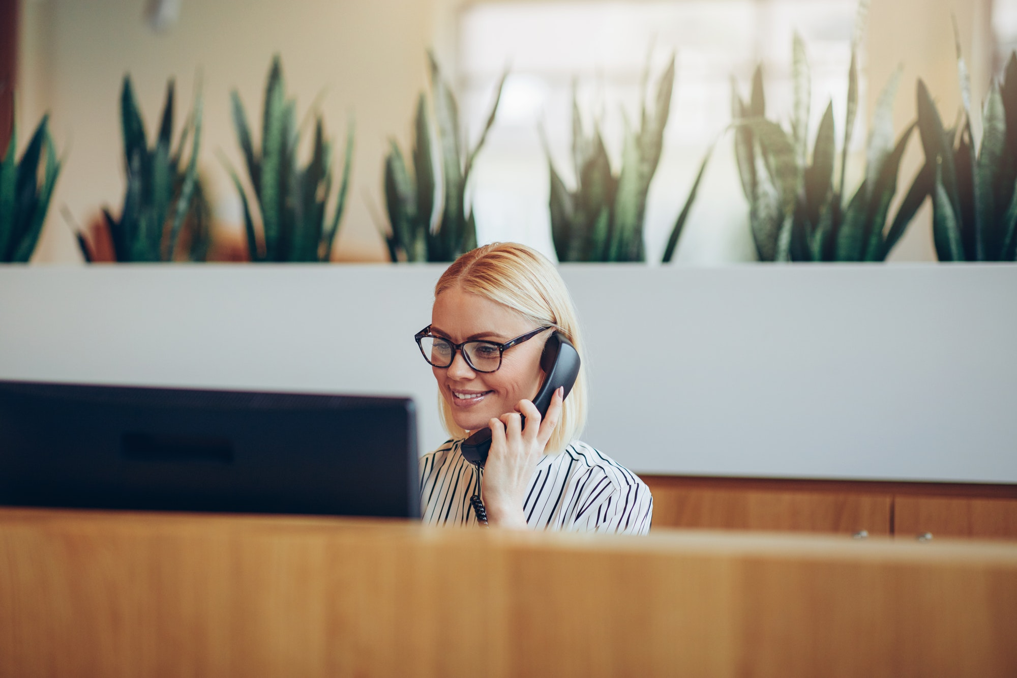 Smiling businesswoman talking on the telephone at a reception desk